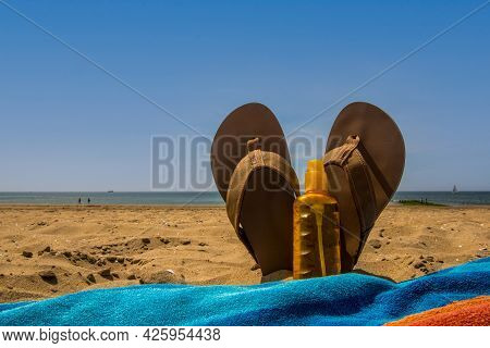 Den Helder, The Netherlands. June 2021. Flip Flops, Sunscreen And A Colorful Towel At The Beach. Bea