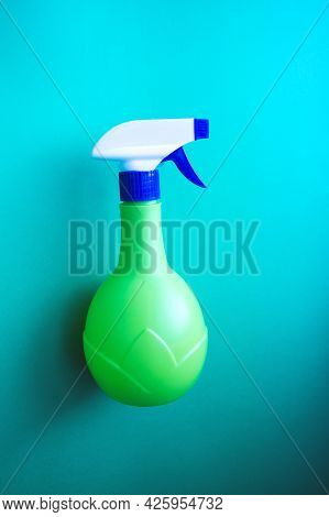 Plastic Spray Yellow Bottle Isolated On Blue Background. Bottle For Detergent Or For Plant Spraying.