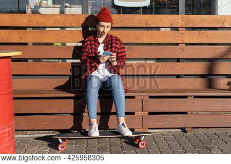 Young Caucasian Girl Skater Chatting In Smartphone Outdoors Sitting On Bench After Longboard Riding.