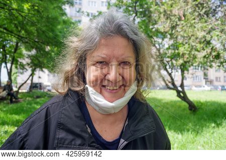 Happy smiling elderly woman in her seventies with protective coronavirus mask under her chin outdoors during spring time.
