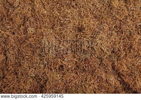 Stack of brown shredded tobacco for pipe or cigarettes, ready to be rolled. Useful for background.