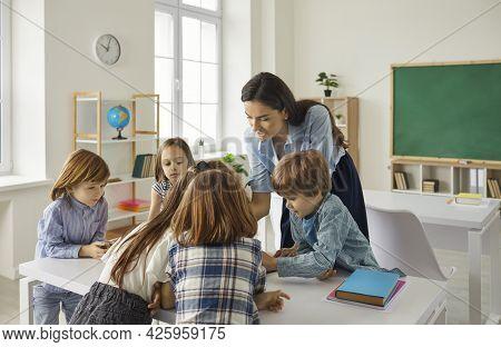 Young Teacher Teaching Schoolchildren Or Preschooler Group In Classroom
