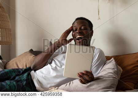 African Guy Sitting On Couch In Cozy Living Room Spending Free Time, Read Joke Message From Friend L
