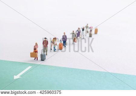 Queue Of Miniature Travellers Crossing Into The Green Travel Zone