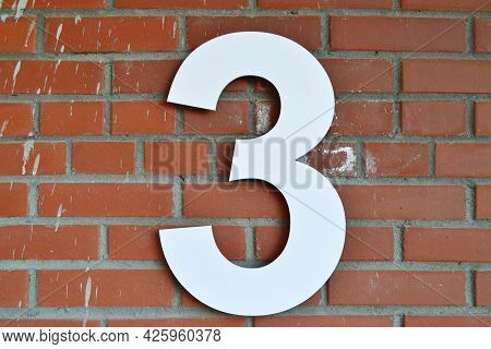 Room 3 Is White, Isolated On A Red Brick Wall.location.street Or House Number Three.stone Texture