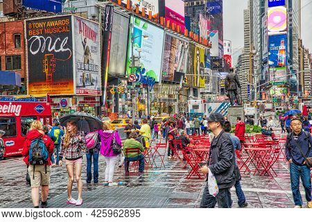 New York, Usa - June 10, 2013: People Visit Ny Times Square In The Rain. Times Square Has Over 39 Mi