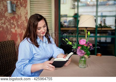 A Woman Sits At A Table In A Cafe Or On The Veranda And Reading A Book Aloud.