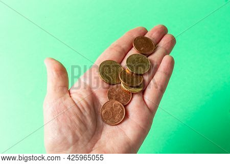 Euro Cents In Hand On Green Background. Poverty Concept. Below The Poverty Line.