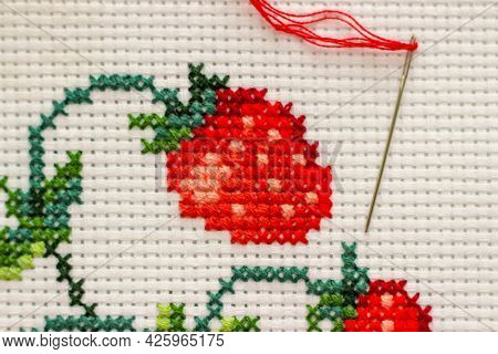 Red Ripe Strawberries Embroidered With A Cross-stich On A White Canvas By Hand. With A Needle And Re