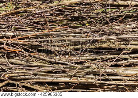 Branches And Twigs. Texture. Natural Background. A Fence Made Of Dry Tree Branches. Country Style.
