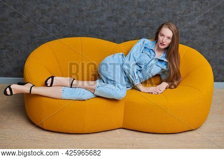 Fashion shot. Beautiful fashion model girl poses in denim overalls on a bright yellow sofa in a modern apartment. Modern interior, furniture.