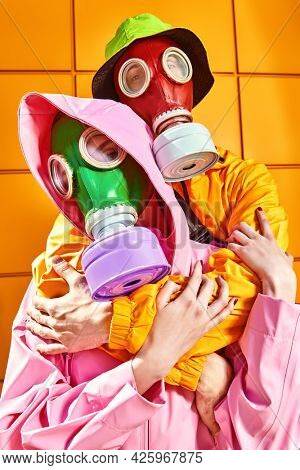 Two tender lovers in bright clothes and gas masks stand hugging each other by a yellow industrial wall. Love and the apocalypse. Environmental disaster.