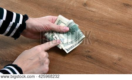 Woman Hands Holding American Cash Banknotes And Pointing By Finger To 100 Dollars Bill Marked By Ink