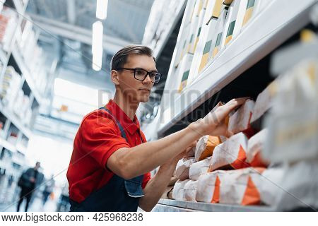 Supervisor Of A Construction Store Checking Brands With Building Mixes.