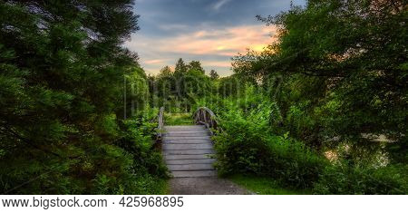 Wooden Bridge Over The Pond On A Walking Path In A Famous Stanley Park. Sunset Summer Sky. Downtown