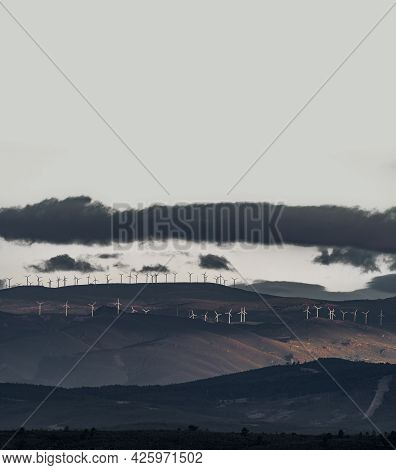 Windmill Farm Over The Hills With Clouds And White Sky