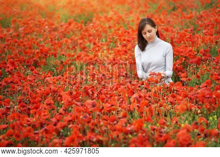 Cute young woman in big meadow of poppies. Emotional and nature scene.