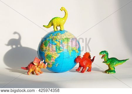Funny Toy Dinosaurs Are Standing Around A Globe - The Globe. The Concept Of Paleontology And The Stu