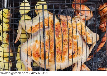 Cooking Chicken On Barbecue Grill. Delicious Golden Roasted Meat And Potatoes. Concept Background Fo