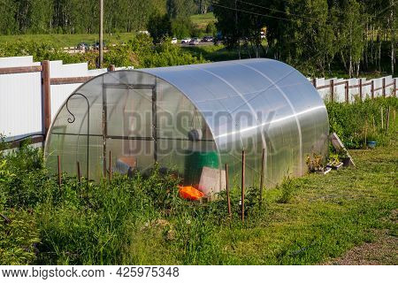 Suburban Area In Russia With A Polycarbonate Greenhouse On A Sunny Summer Day. Home Gardening