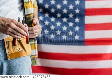 Partial View Of Workman In Tool Belt Holding Pliers Near Blurred Usa Flag, Labor Day Concept