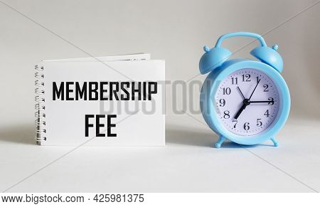 On Notepad Text About Membership Fee, Business Concept Image On White Background With Alarm Clock