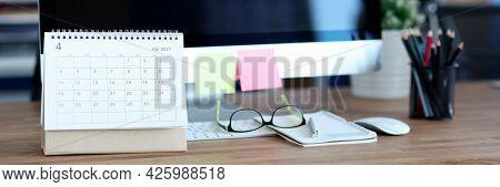 Loose Leaf Paper Calendar Standing Near Computer On Desktop Closeup