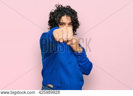 Young hispanic woman with curly hair wearing turtleneck sweater punching fist to fight, aggressive and angry attack, threat and violence