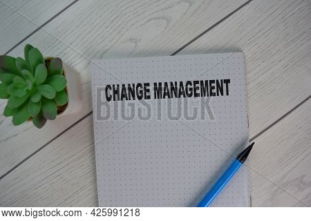 The Book Of Change Management Isolated On Wooden Table.