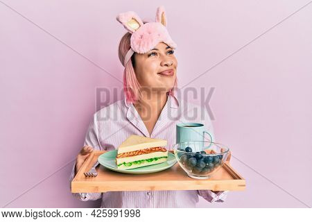 Hispanic woman with pink hair wearing pajama holding healthy breakfast smiling looking to the side and staring away thinking.
