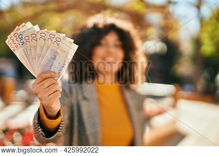 Young hispanic businesswoman smiling happy holding swedish krone banknotes at the city.