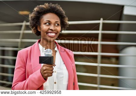 Young african american woman journalist holding reporter microphone speaking and smiling to the camera for television news