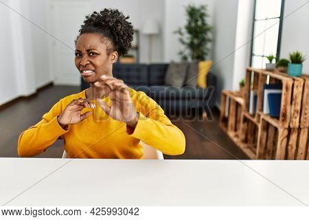 Young african american woman wearing casual clothes sitting on the table at home disgusted expression, displeased and fearful doing disgust face because aversion reaction. with hands raised