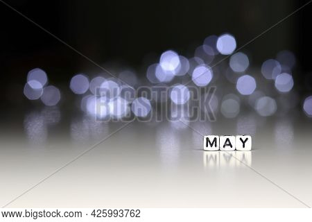 May Is A Word Written On A White Block. May Be The Word For Your Design, Concept. Beautiful Bokeh In