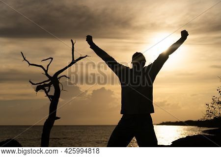 Happy Exited Man Jumping On Sea And Beautiful Sunrise Background. Happiness, Joy And Success Concept