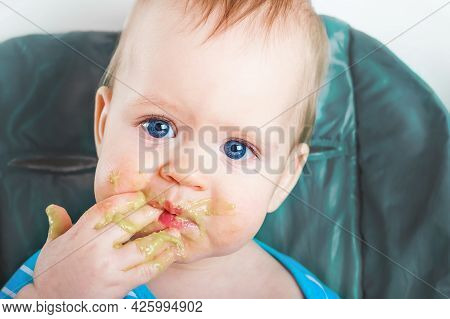 Handsome Toddler Licks His Hand Close-up. Baby Complementary Feeding, Food Allergy, Intolerance Conc
