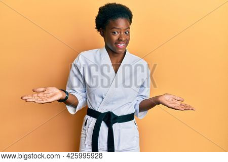 Young african american girl wearing karate kimono and black belt clueless and confused expression with arms and hands raised. doubt concept.