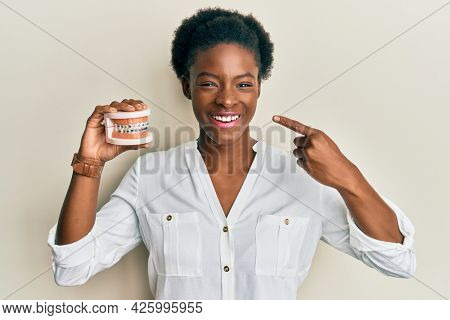 Young african american girl holding orthodontic smiling and laughing hard out loud because funny crazy joke.