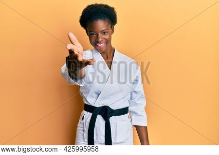 Young african american girl wearing karate kimono and black belt smiling friendly offering handshake as greeting and welcoming. successful business.