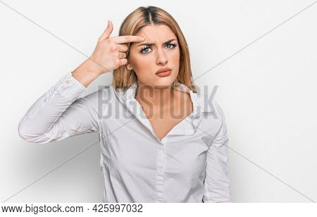 Young caucasian woman wearing casual clothes pointing unhappy to pimple on forehead, ugly infection of blackhead. acne and skin problem
