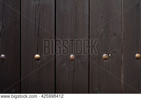 Fragment Of A Wooden Plank Fence With Metal Rivets. Background With Copy Space. Close-up