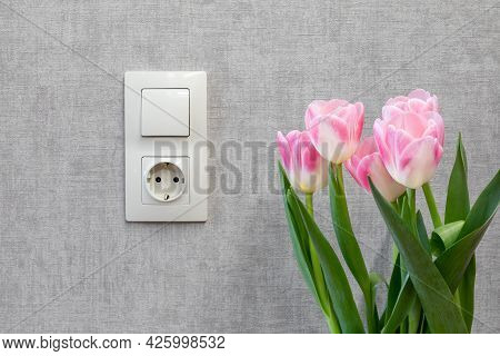 A Electric Light Switch And A Grounded Outlet On An Empty Gray Wall. A Bouquet Of Tulips Against The