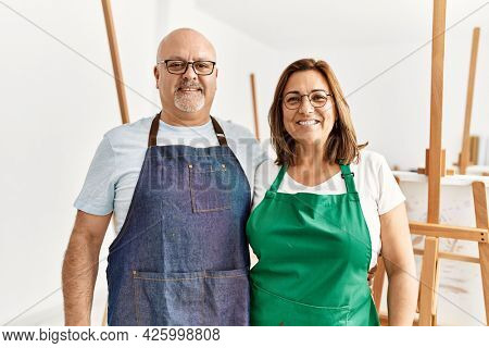 Middle age hispanic painter couple smiling happy standing at art studio.