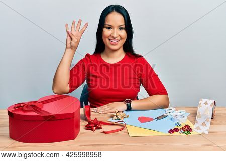Beautiful hispanic woman with nose piercing doing handcraft creative decoration showing and pointing up with fingers number four while smiling confident and happy.