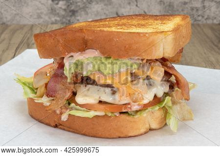 Enormous Texas Toast Sandwich Loaded With Hamburger, Cheese, Lettuce, Bacon, And Special Sauce For T