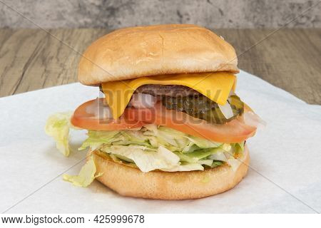 Junior Sized Cheeseburger Stacked Tall With Lettuce, Tomato And Cheese For The Kids Appetite.