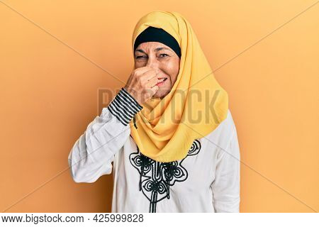 Middle age hispanic woman wearing traditional islamic hijab scarf smelling something stinky and disgusting, intolerable smell, holding breath with fingers on nose. bad smell