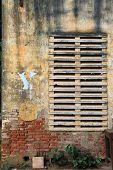 Weathered wall with bricks and grate in Battambang Cambodia. poster