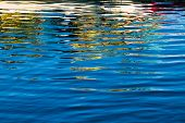 Multiple colors reflected in rippling blue water. poster