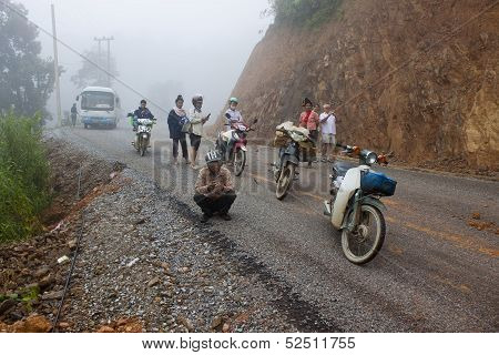 People wait for clearing a road after landslide on